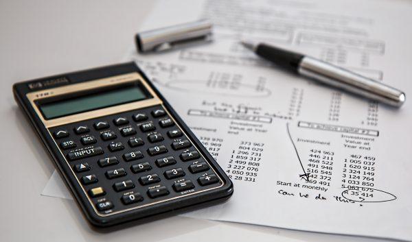 A calculator, expense sheet, and pen