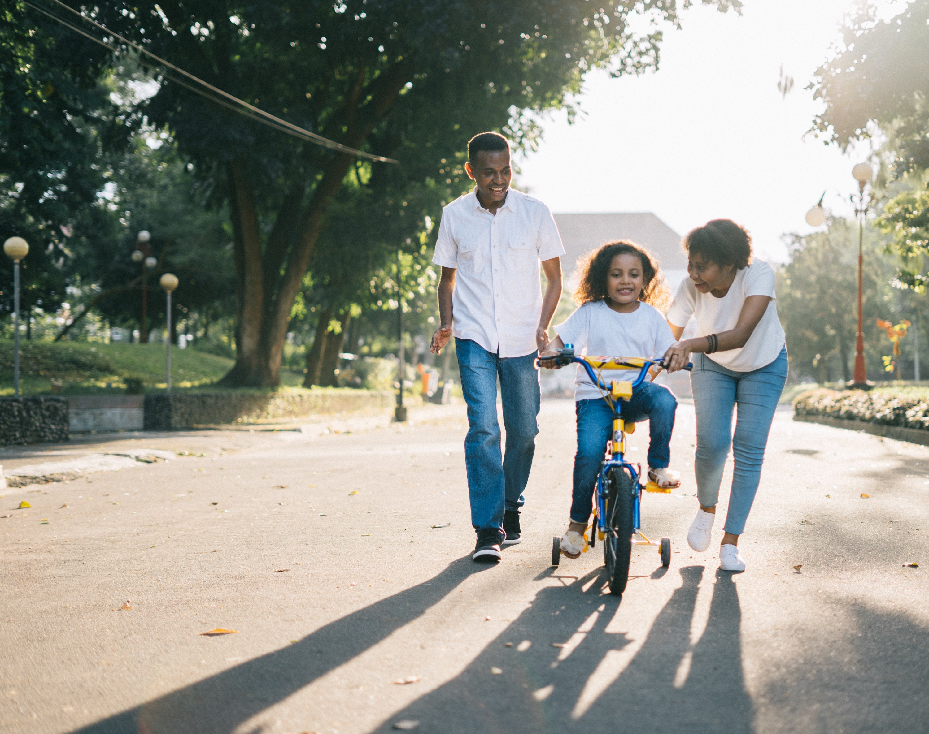 Black family of 3 all wearing blue jeans and white tops while smiling and teaching their daughter how to ride a bike