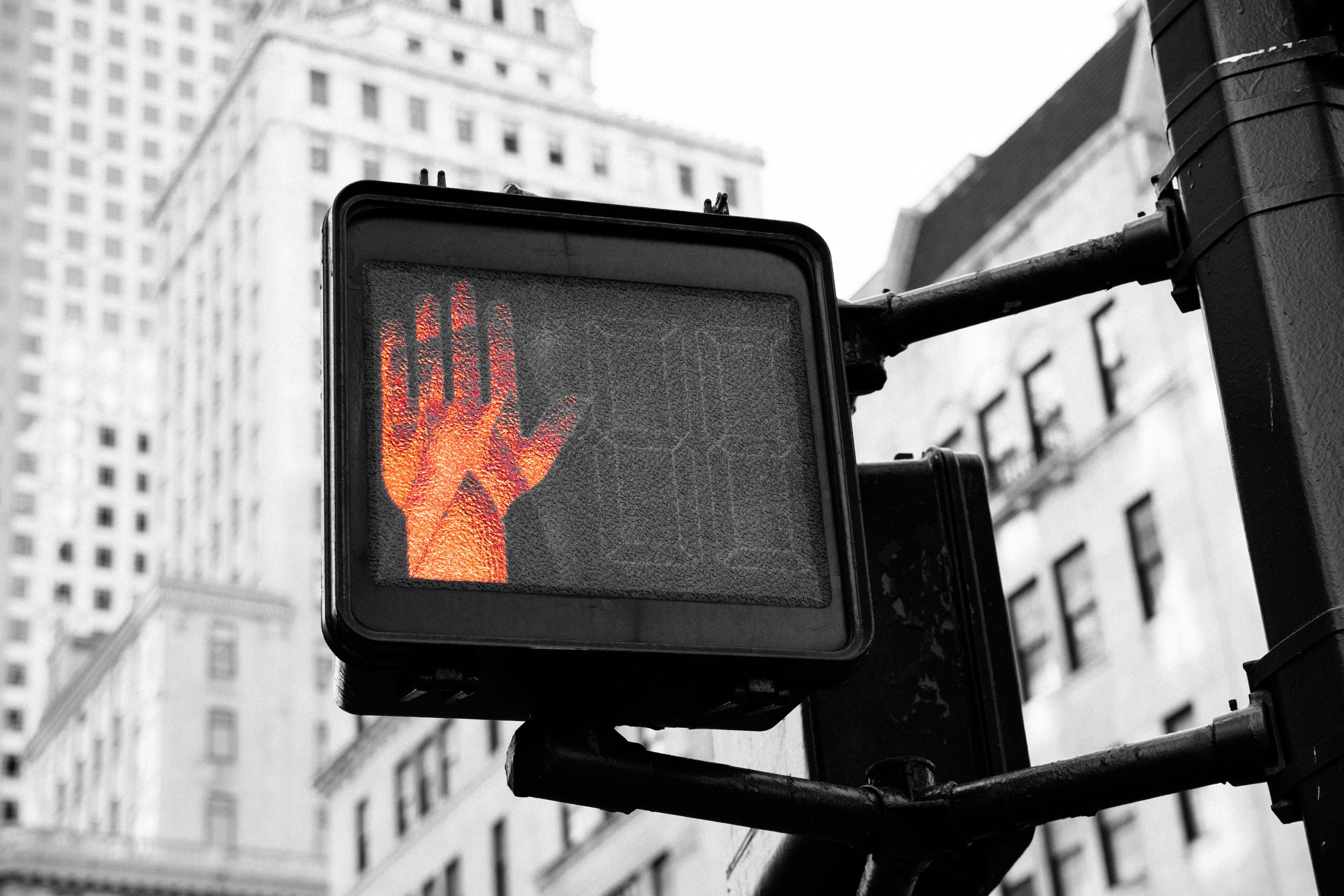Black and white photo of a street crossing sign with the stop hand signal in red