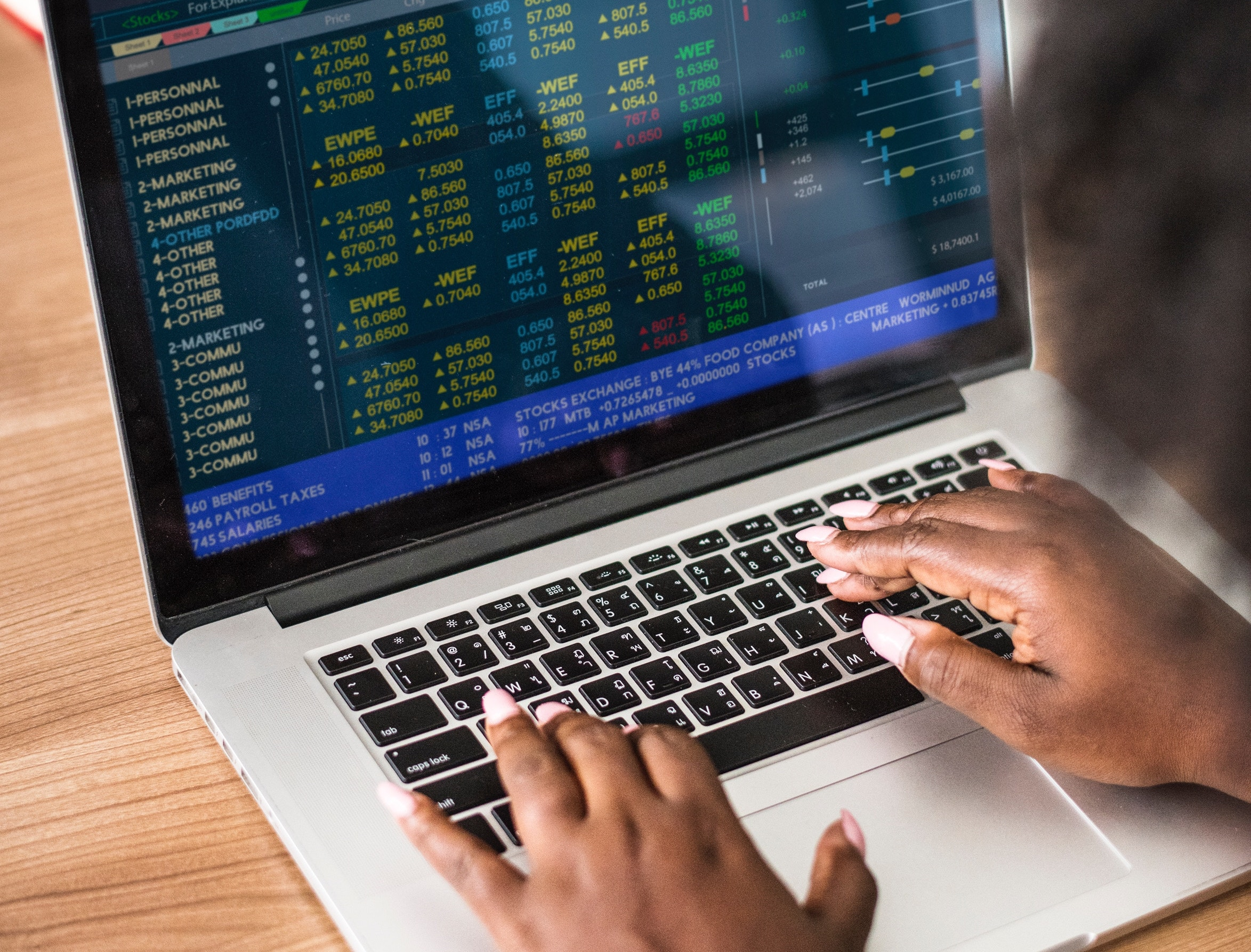 Black woman types on her laptop while her screen shows updated stock market numbers