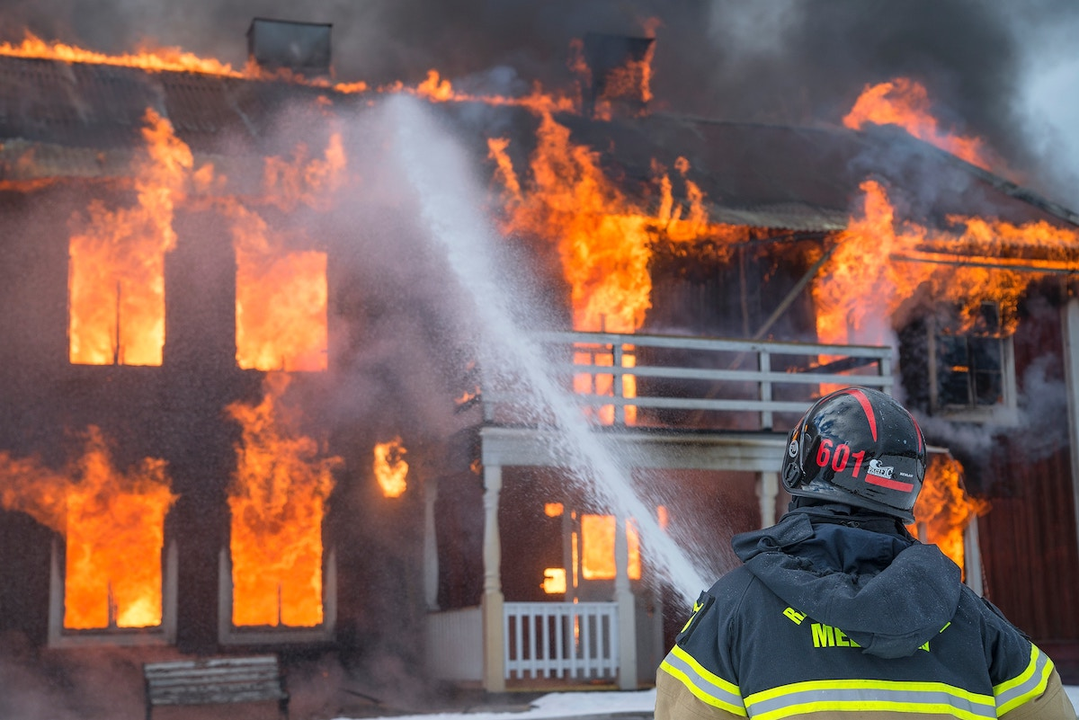 Firefighter in black and yellow suit aims his hose at a building that's up in flames