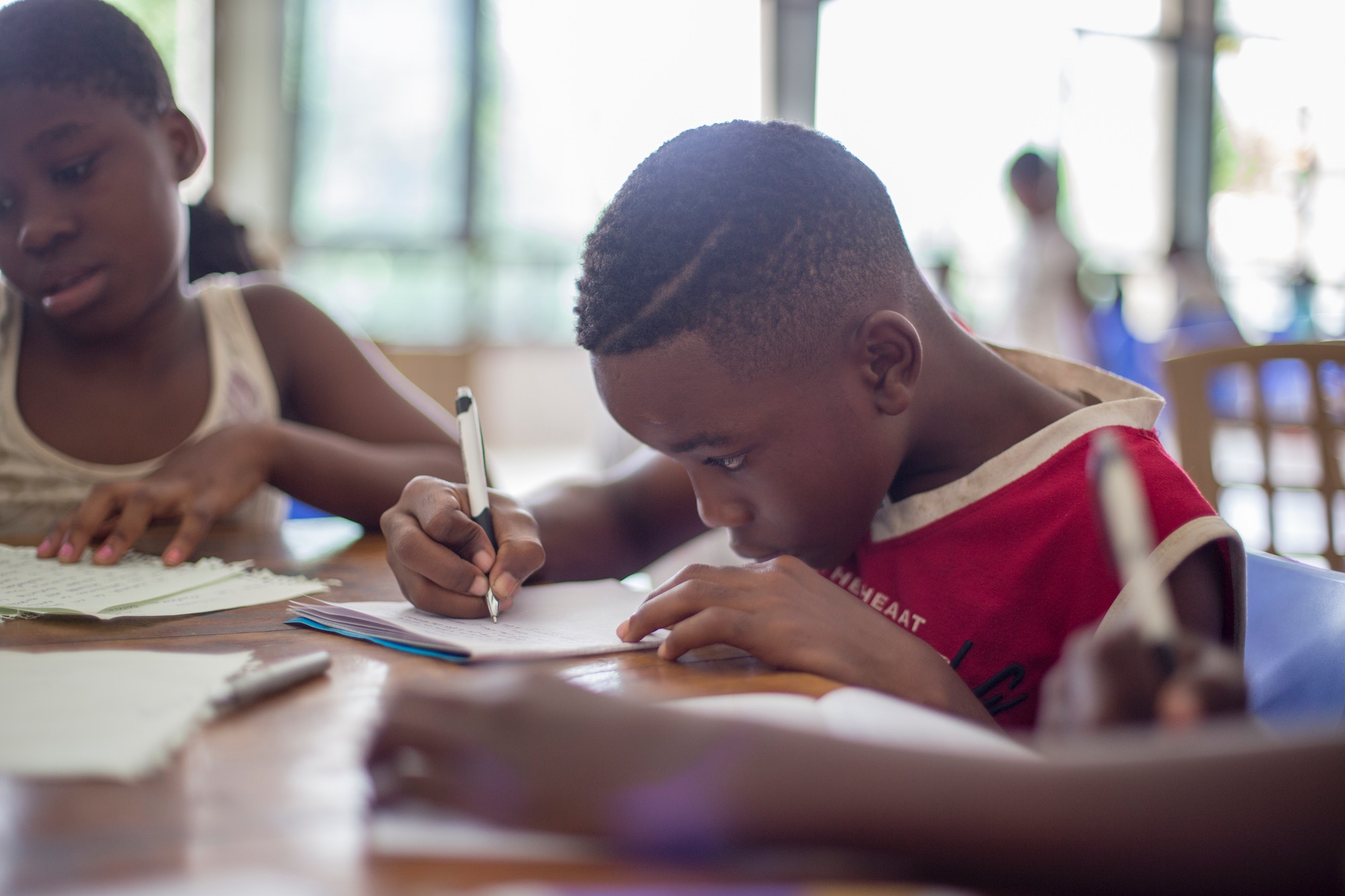 Three black children sit down to do their homework