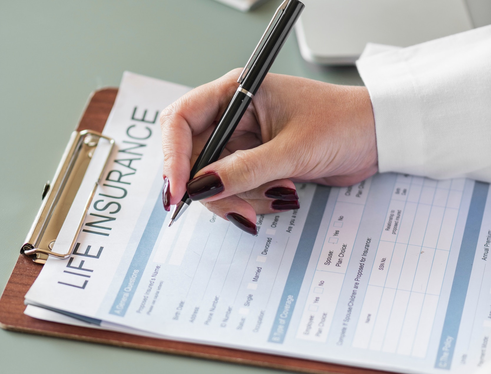 White woman with wine colored nails holds a pen while she fills out a life insurance form