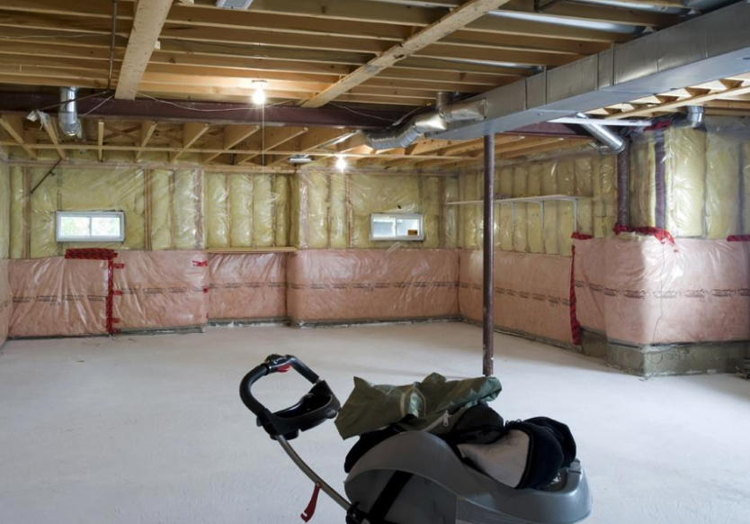 Unfinished basement with pink and yellow insulation asbestos plastered against the walls