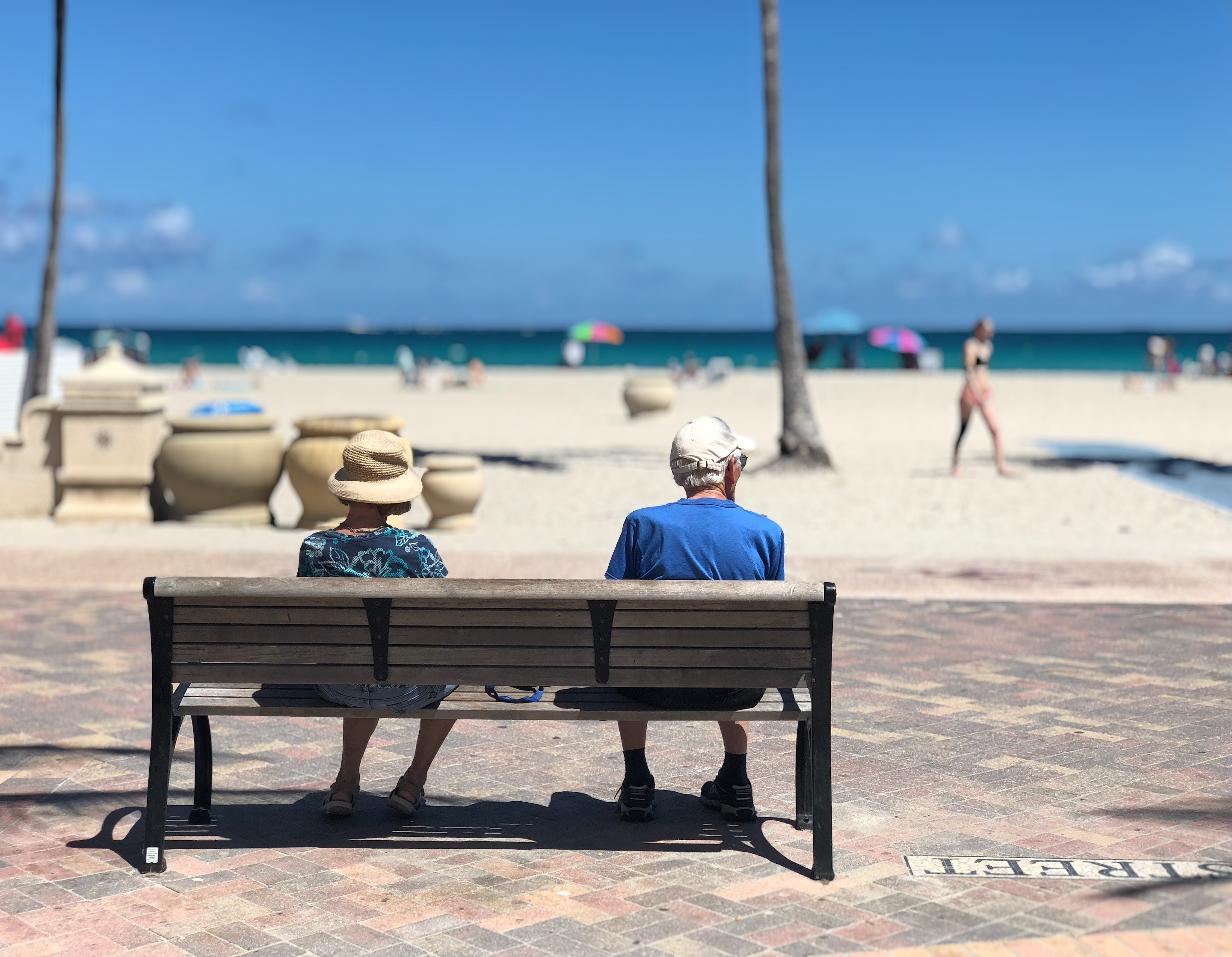 Older white couple sits on a bench on a beach sidewalk looking at the passerby