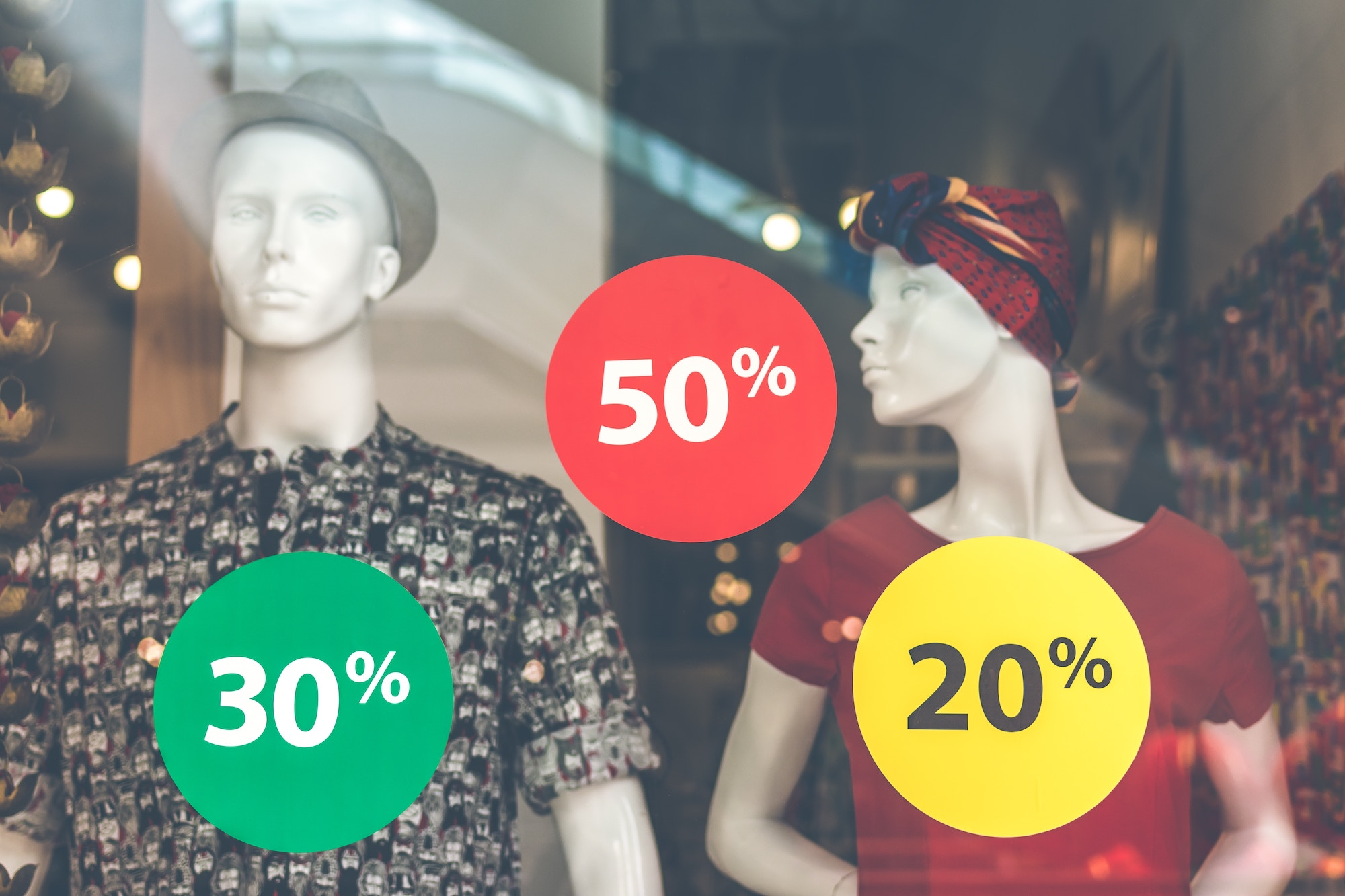 Storefront of two mannequins with stickers showing various percentages indicating a sale