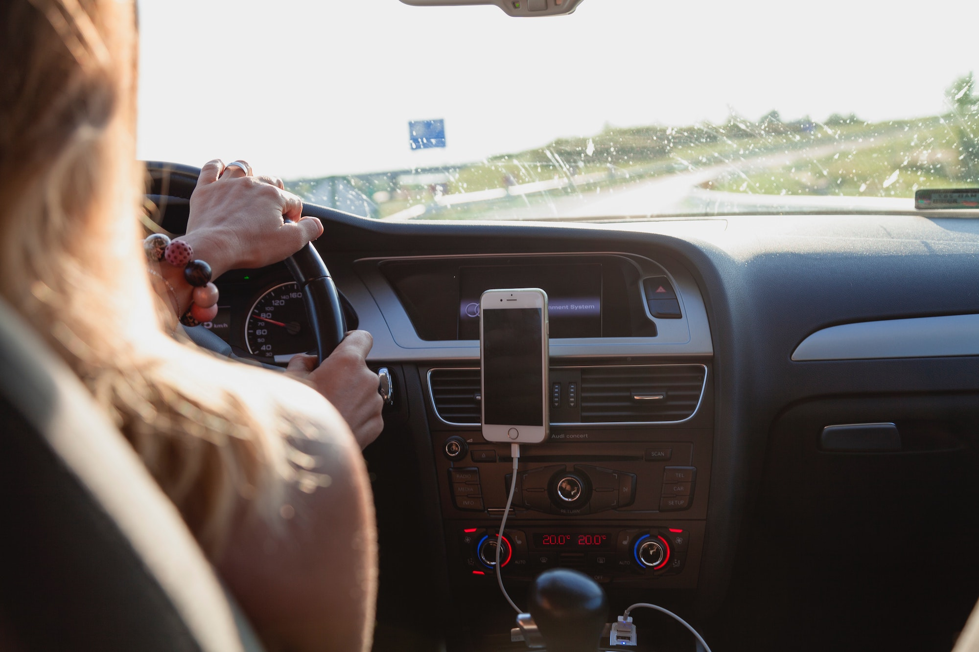 Blonde-haired woman driving on an open road
