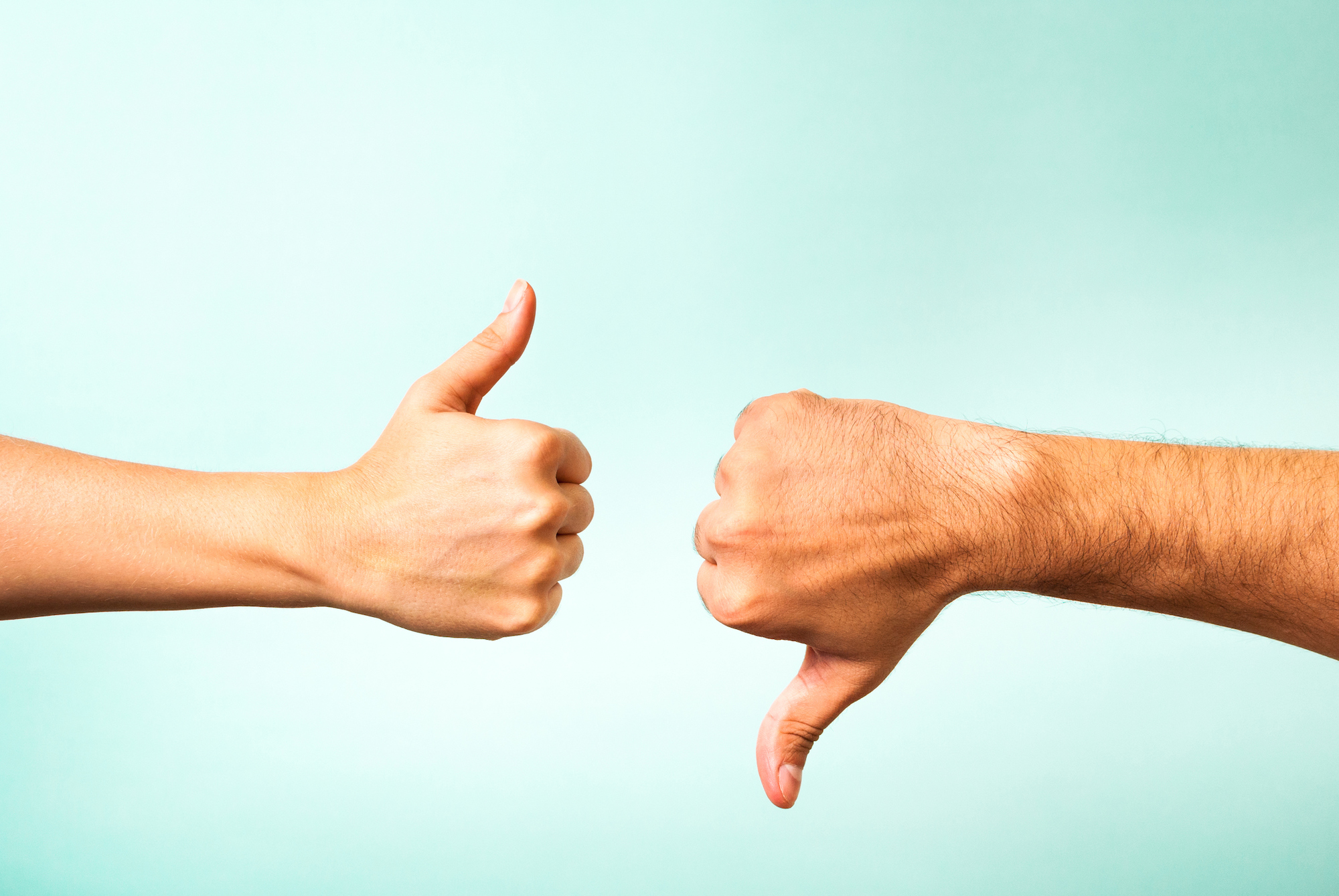 A woman's hand gives a thumbs up opposite of a man's hand giving a thumbs down on a teal background