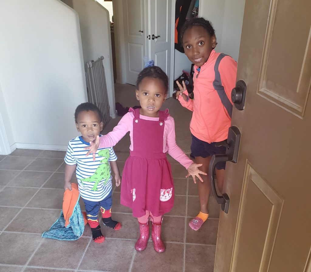 Three black children standing in the entryway of a house all pose for a picture before they head to school