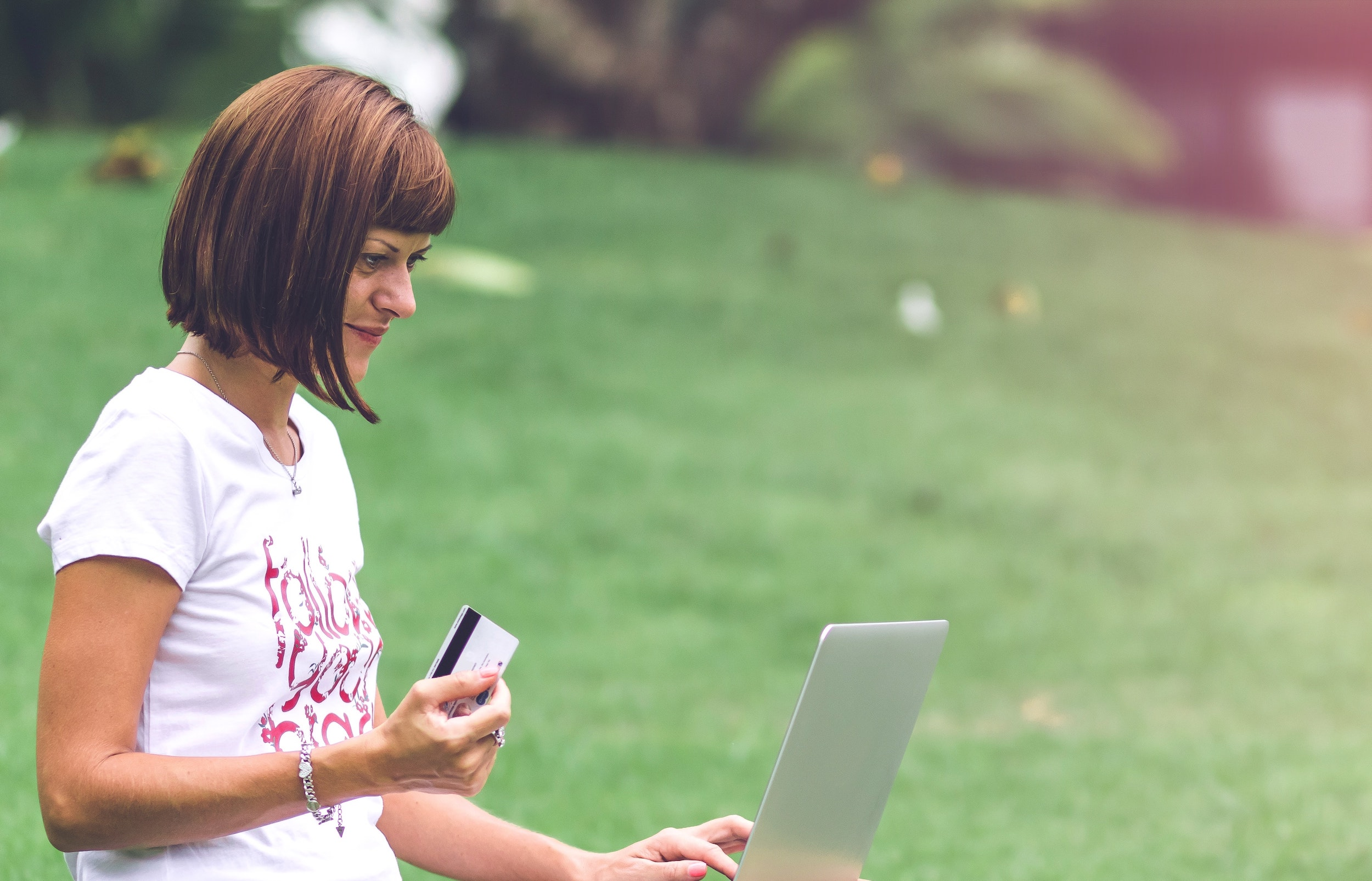 White woman with a short bob haircut and wearing a graphic white t-shirt sits in a meadow with her laptop in her lap and holding her credit card