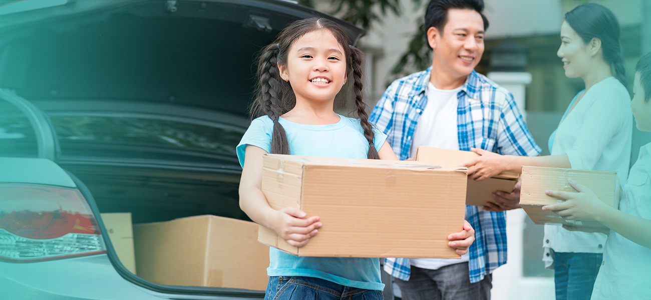 Girl in pigtails holding a box smiles for the camera while her parents are holding boxes and helping move their family into the house