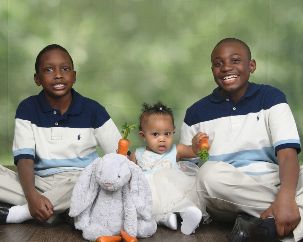 Two young black boys wearing Tommy Hilfiger striped polos smile while sitting on either side of their infant cousin who is wearing a blue and white dress and holding carrots in both her hands