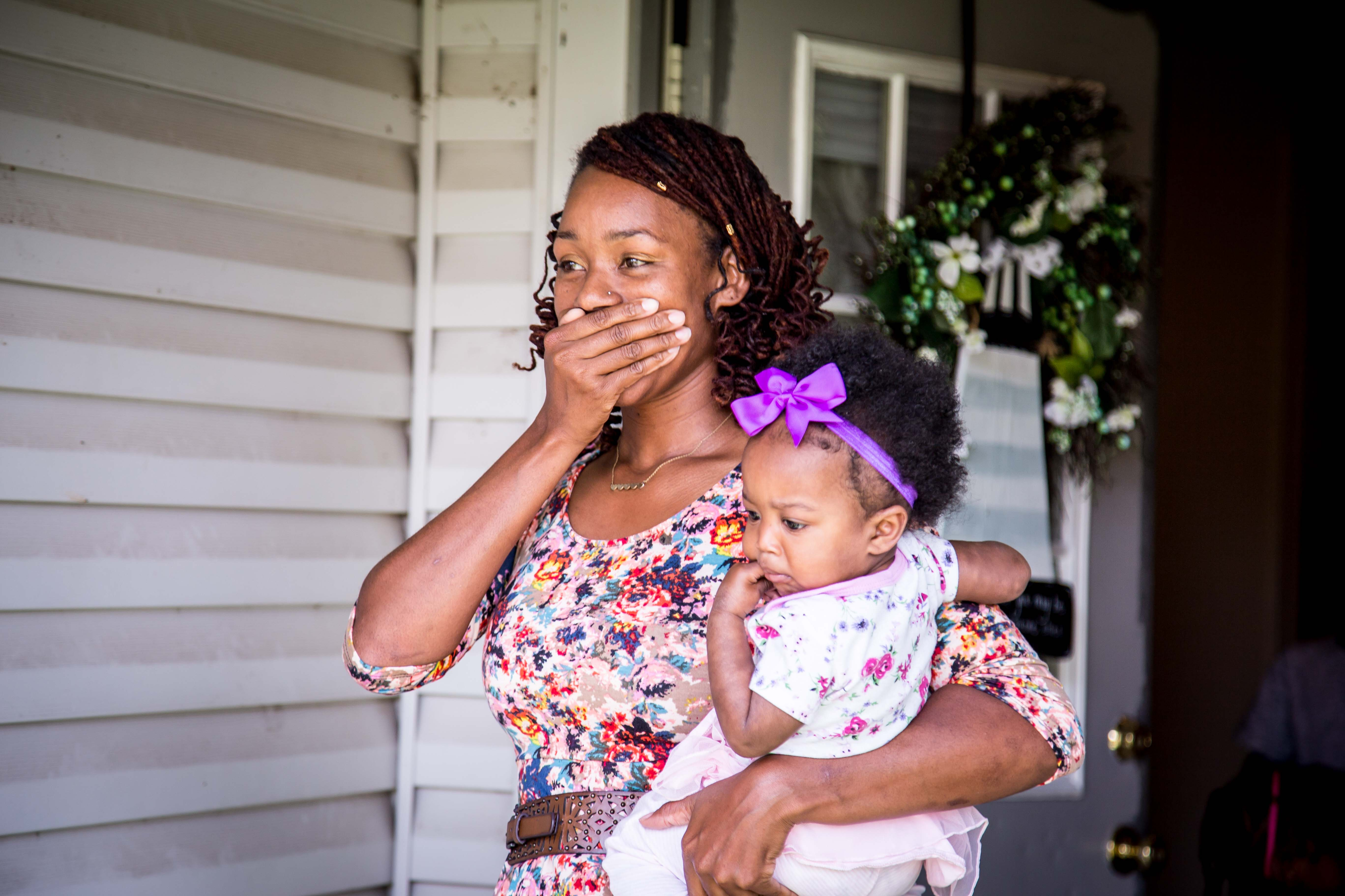 Black woman in a flowery short sleeve dress holds her baby with her left arm while covering her mouth in surprise with her right hand