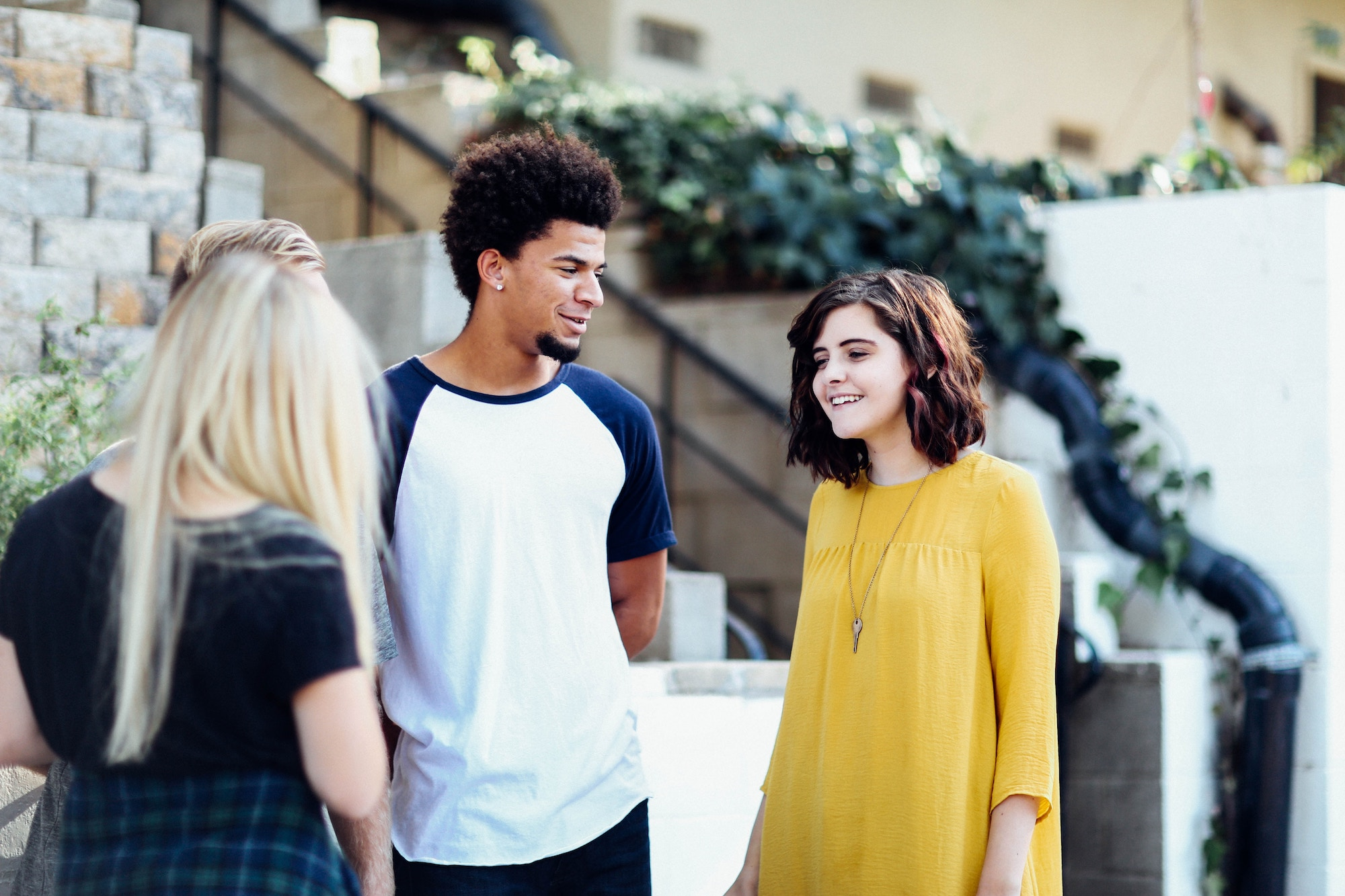 White girl wearing a yellow flowy dress and necklace smiles while talking to a black man wearing a blue and white baseball t-shirt while a blonde-haired woman has her back turned to the camera