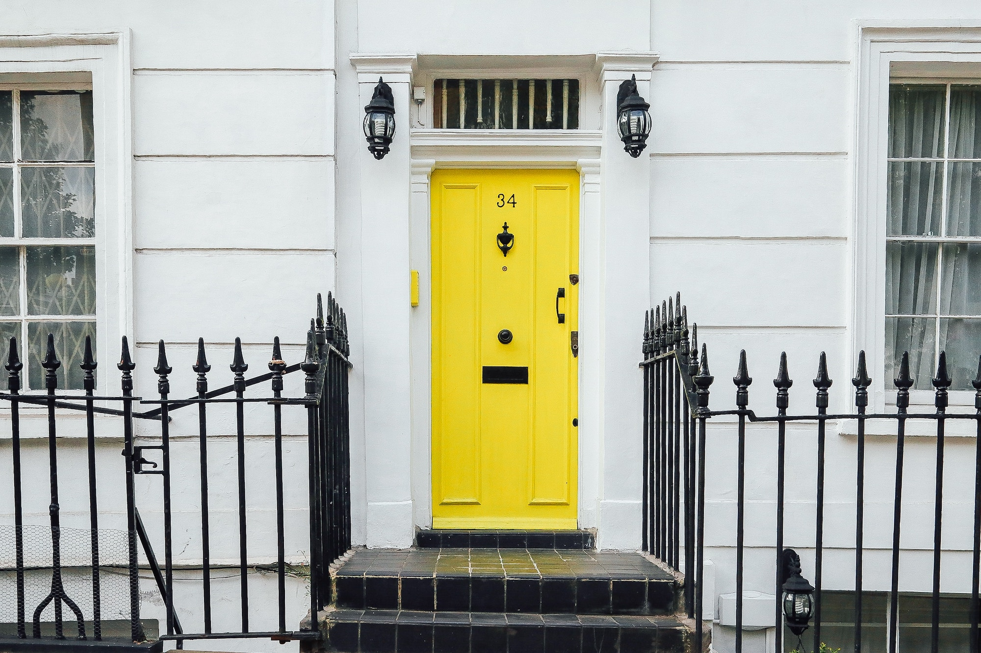 Symmetrical photo of a yellow door of a white house with fences on either side