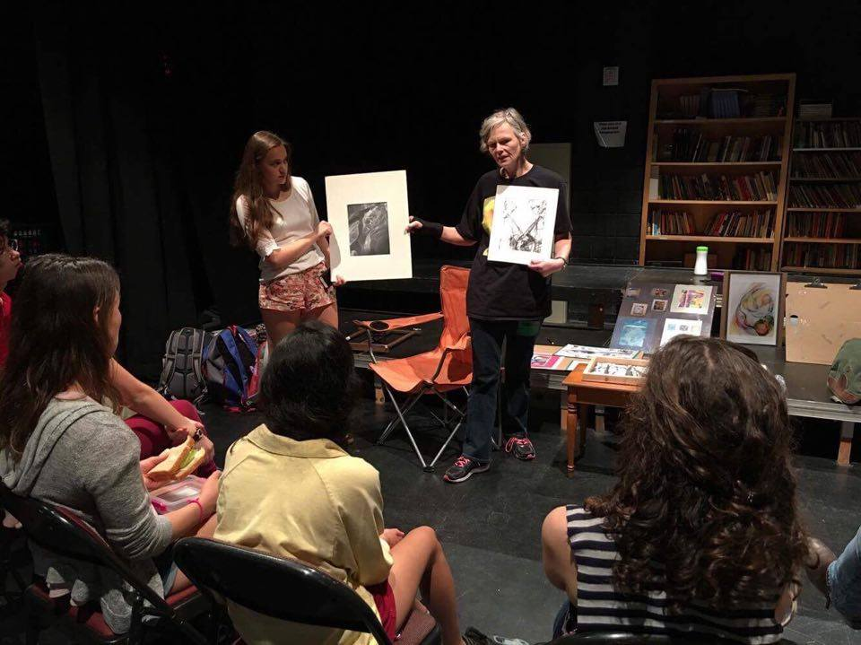 An older gray-haired woman shows her drawings to art students in a class while wearing a black graphic t-shirt, dark, jeans, and running shoes