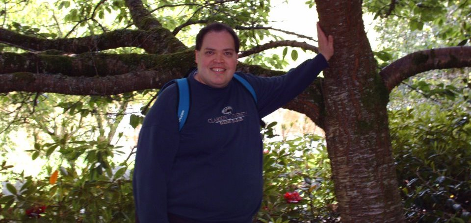 Tall man smiles while wearing a dark blue sweatshirt and carrying a light blue backpack leans one arm against a tree