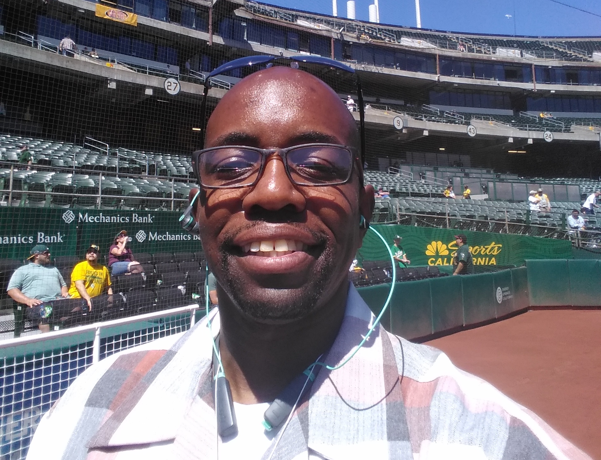 Black man with glasses wearing a checkered polo takes a selfie on the field of an empty baseball field on a sunny day