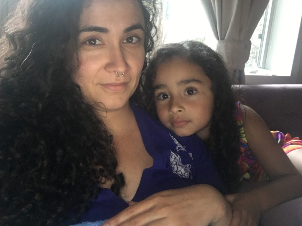Curly haired woman with a septum nose ring takes a selfie with her daughter