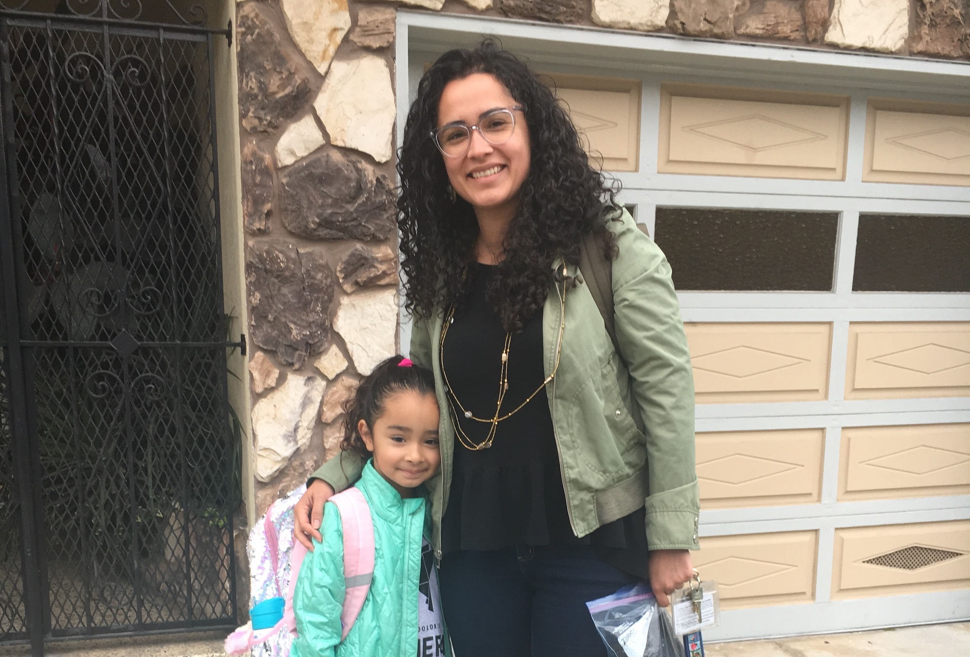 A woman with curly hair and glasses wearing a black dress and light green jacket side hugs her daughter who is wearing a teal blue jacket and backpack in front of their apartment