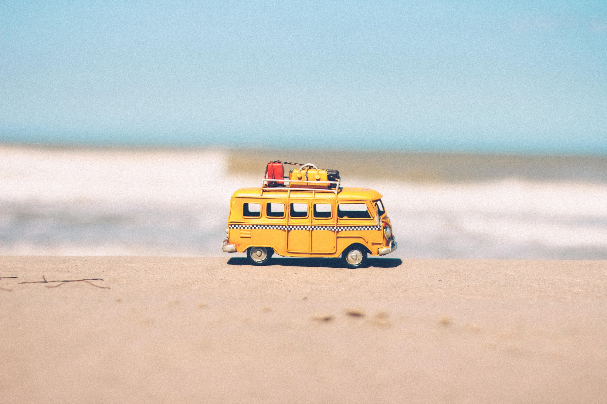 Yellow toy van carrying luggages placed on the sand of a beach with the waves crashing in the background
