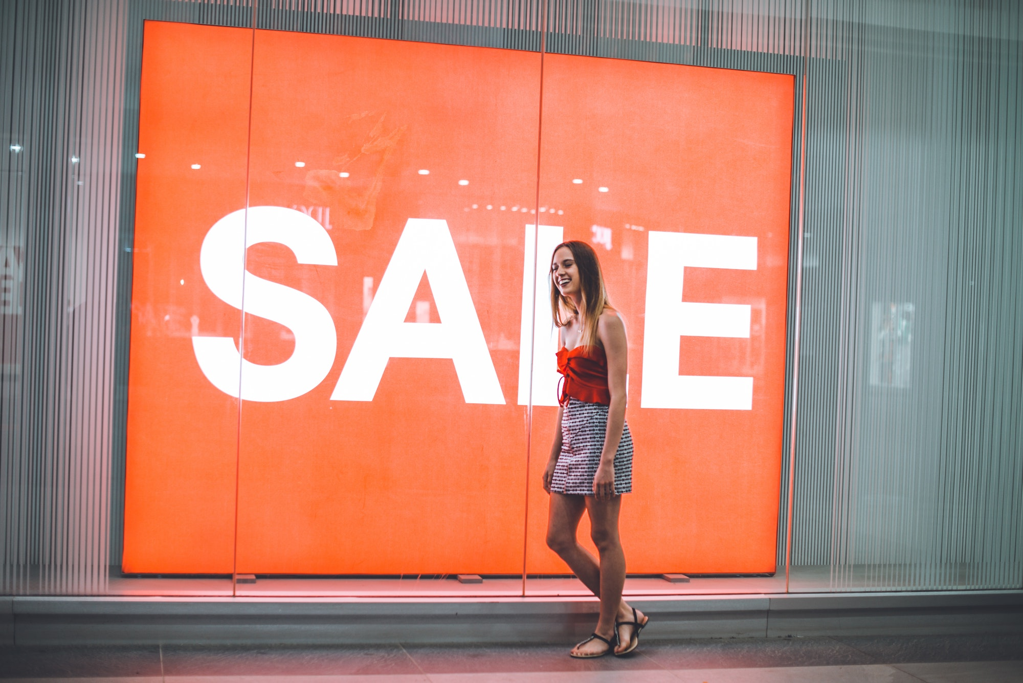 Thin girl smiling while leaning on a glass storefront that reads SALE and wearing a red tank top, checkered skirt, and black sandals