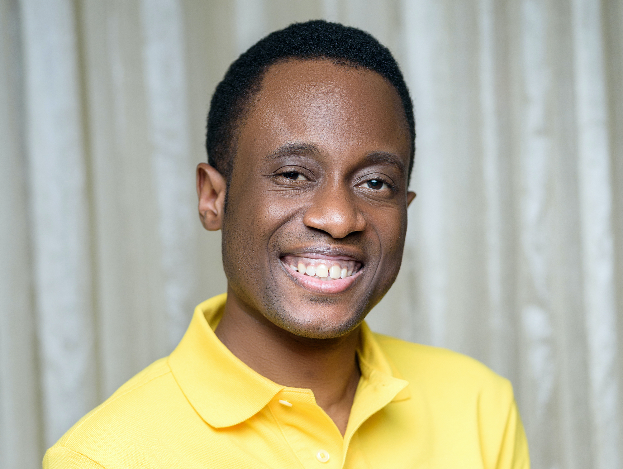 Headshot of an African-American man in a professional studio who wearing a yellow polo and smiling