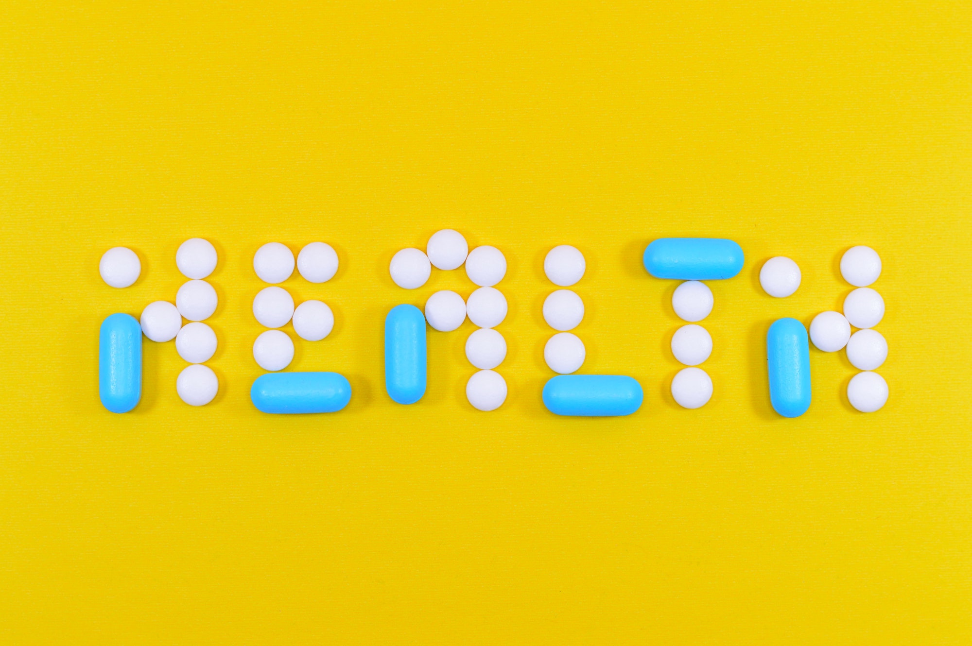 White circular pills and small blue capsule pills are arranged on a canary yellow background and spell the word HEALTH