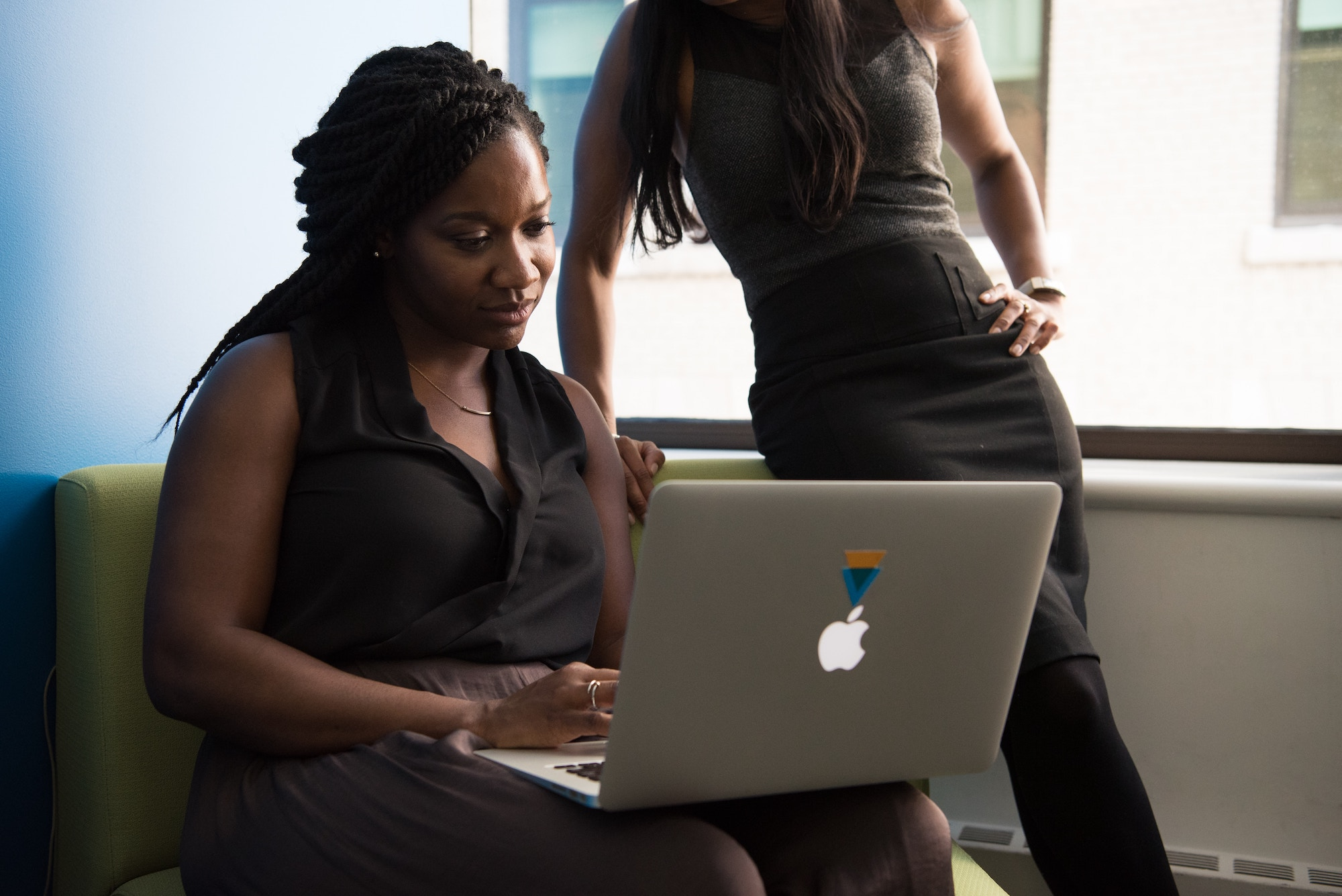 Black woman in a professional black tank top and pleated skirt sits down with a laptop while a woman in a similar outfit looks at the laptop screen