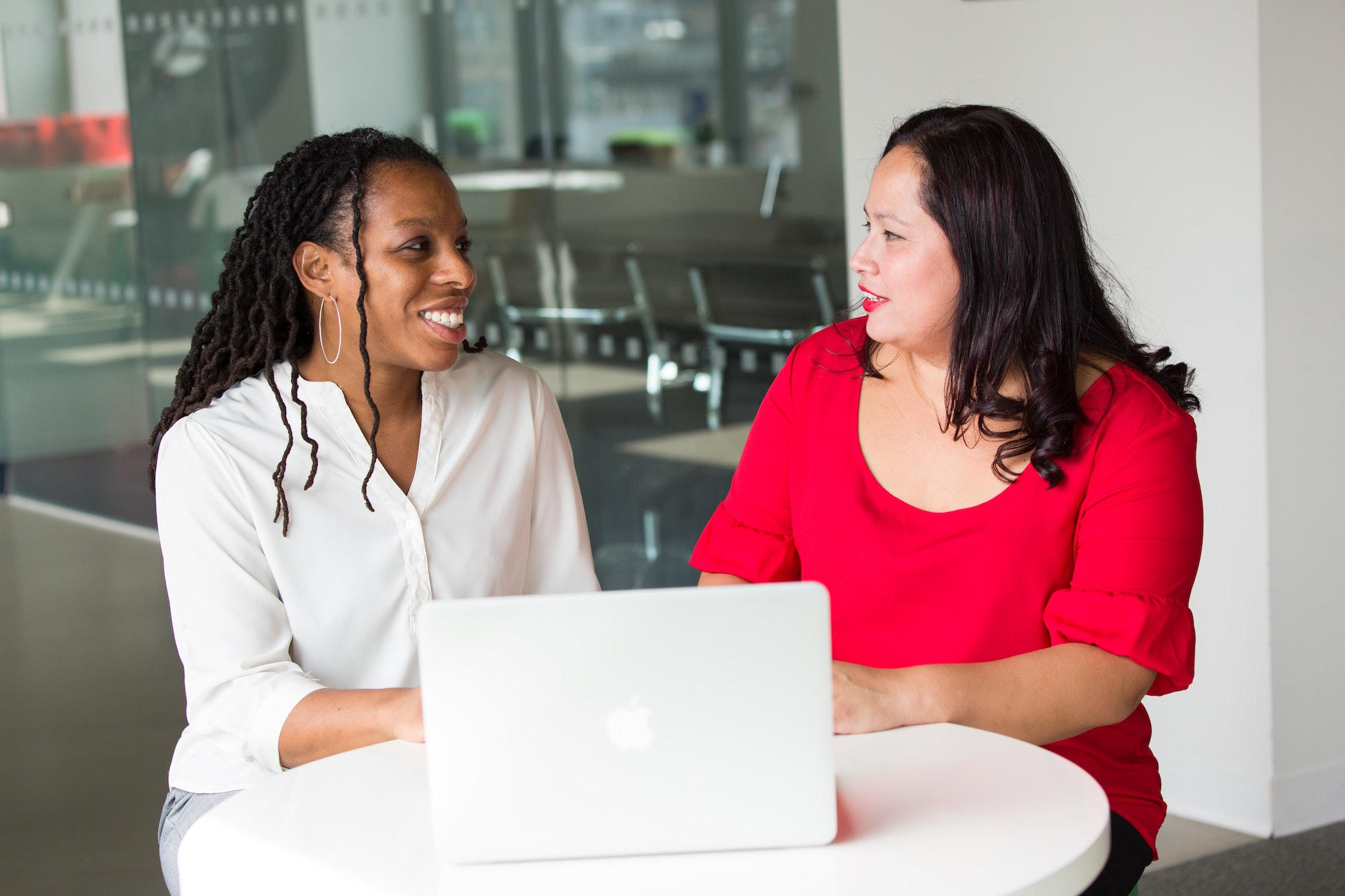 Black woman in a white button down shirt smiling and talking to an Asian woman in a red dress in an office setting