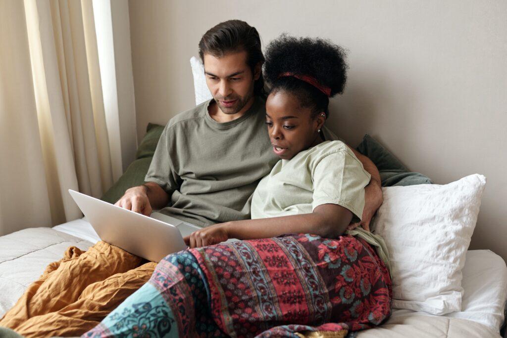 Couple looking at budget and debt in bed small