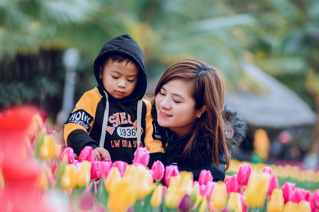 Mother and son playing in tulips