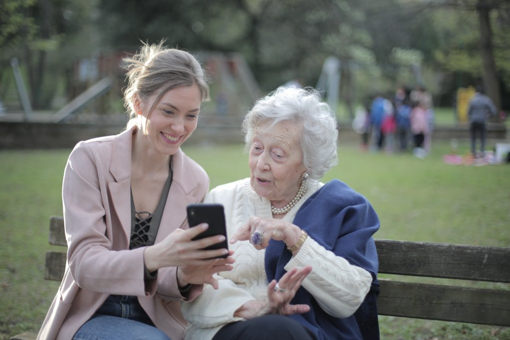 Woman showing another woman how to use a phone savings account